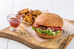 Fast food dish. Appetizing meat burger, potato chips and sauce. Takeaway composition. Royalty Free Stock Photo