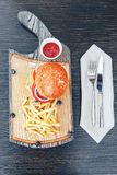 Fast food dish. Burger with fries on a wooden cutting board. Delicious hamburger and french fries with sauces royalty free stock photography
