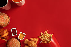 Fast food dish top view. Meat burger, potato chips and glass of drink on red background. Takeaway composition. Stock Images