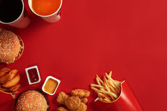 Fast food dish top view. Meat burger, potato chips and glass of drink on red background. Takeaway composition. Stock Image