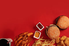 Fast food dish top view. Meat burger, potato chips and glass of drink on red background. Takeaway composition. Stock Photo