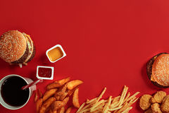 Fast food dish top view. Meat burger, potato chips and glass of drink on red background. Takeaway composition. Royalty Free Stock Photo