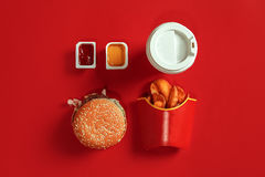 Fast food dish top view. Meat burger, potato chips and glass of drink on red background. Takeaway composition. Stock Photography