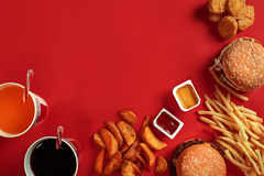 Fast food dish top view. Meat burger, potato chips and glass of drink on red background. Takeaway composition. Stock Photos