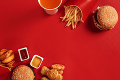 Fast food dish top view. Meat burger, potato chips and glass of drink on red background. Takeaway composition. Royalty Free Stock Photography