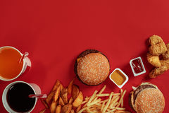 Fast food dish top view. Meat burger, potato chips and glass of drink on red background. Takeaway composition. Royalty Free Stock Images