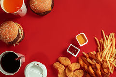 Fast food dish top view. Meat burger, potato chips and glass of drink on red background. Takeaway composition. Royalty Free Stock Photos