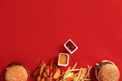 Fast food dish top view. Meat burger, potato chips and nuggets on red background. Takeaway composition. Top view Stock Photos