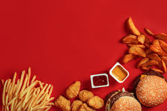 Fast food dish top view. Meat burger, potato chips and nuggets on red background. Takeaway composition. Stock Image