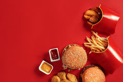 Fast food dish top view. Meat burger, potato chips and nuggets on red background. Takeaway composition. Royalty Free Stock Images