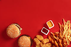 Fast food dish top view. Meat burger, potato chips and nuggets on red background. Takeaway composition. Stock Photo