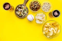 Fast food dla TV dopatrywania Przekąski na biurku Układy scaleni, dokrętki, rusks i piwo na żółtej tło odgórnego widoku kopii prz zdjęcie royalty free