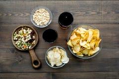 Fast food dla TV dopatrywania Przekąski na biurku Układy scaleni, dokrętki, rusks i soda na ciemnego drewnianego tła odgórnym wid obrazy stock