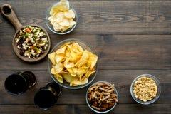 Fast food dla TV dopatrywania Przekąski na biurku Układy scaleni, dokrętki, rusks i soda na ciemnej drewnianej tło odgórnego wido zdjęcia stock