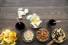 Fast food dla TV dopatrywania Przekąski na biurku Układy scaleni, dokrętki, rusks i soda na ciemnej drewnianej tło odgórnego wido obrazy stock