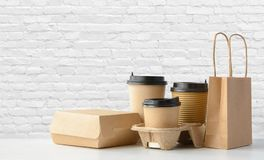 Fast food and drink packaging set. Fast food packaging set. Paper coffee cups in holder, food box, brown paper bag on the table Stock Image