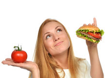 Fast food eating concept comparing burger sandwich in hand and t Stock Photography