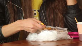 Fast-food eating with fork, drinking coffee, young adult woman stock video