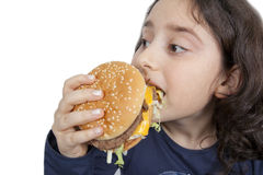 Fast food eating teen girl. A child is eating a hamburger with a great appetite Royalty Free Stock Photography