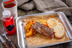 Fast food em um restaurante Um bife bem-fritado com batatas fritas friáveis douradas e almoço combinado brindado do brinde friáve fotografia de stock royalty free