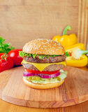 Fast food. Fresh tasty burger on wooden stand royalty free stock image