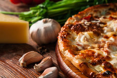 Fast food. Fresh tasty pizza on wooden table. Delicious hot pizza sliced and served on rustic wooden background with ingredients, close up view. Traditional Royalty Free Stock Image