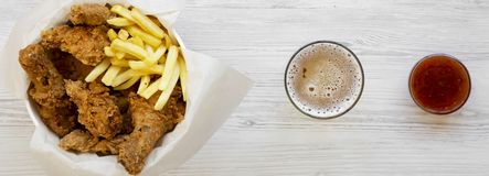 Fast food: fried chicken drumsticks, spicy wings, French fries and chicken strips in paper box, sauce and cold beer over white woo. Den surface, top view. Flat stock photo