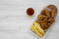 Fast food: fried chicken legs, spicy wings, French fries and chicken strips with sour-sweet sauce over white wooden background,. Top view. Flat lay, overhead stock photography