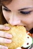 Fast food girl. Pretty girl eating a fast food hamburger Royalty Free Stock Image