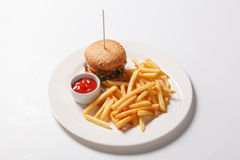 Fast food hamburger and french fries on a white plate Royalty Free Stock Photography