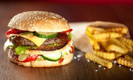 Fast food hamburger and french fries on a wooden Background. Fast food hamburger and french fries on a wooden Background royalty free stock photo