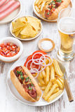 Fast food - hot dog with French fries, beer and snacks, vertical Royalty Free Stock Photography