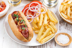 Fast food - hot dog with French fries and chips on wooden table Royalty Free Stock Images