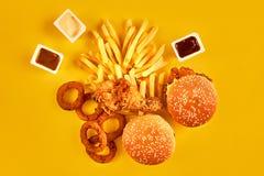 Fast food i niezdrowy łasowania pojęcie - zakończenie up fast food przekąski na żółtym tle Fotografia Stock