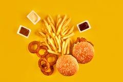 Fast food i niezdrowy łasowania pojęcie - zakończenie up fast food przekąski na żółtym tle Zdjęcia Royalty Free