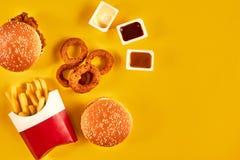 Fast food i niezdrowy łasowania pojęcie - zakończenie up fast food przekąski na żółtym tle Zdjęcie Stock