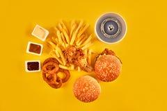 Fast food i niezdrowy łasowania pojęcie - zakończenie up fast food przekąski i zimny napój na żółtym tle Obraz Royalty Free