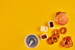Fast food i niezdrowy łasowania pojęcie - zakończenie up fast food przekąski i zimny napój na żółtym tle Fotografia Stock