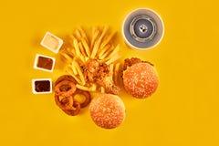 Fast food i niezdrowy łasowania pojęcie - zakończenie up fast food przekąski i zimny napój na żółtym tle Fotografia Royalty Free
