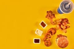 Fast food i niezdrowy łasowania pojęcie - zakończenie up fast food przekąski i zimny napój na żółtym tle Zdjęcie Royalty Free