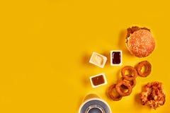 Fast food i niezdrowy łasowania pojęcie - zakończenie up fast food przekąski i zimny napój na żółtym tle Zdjęcia Stock