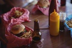 Fast food i piwna butelka na stole Obrazy Royalty Free