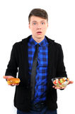 Fast food. Isolated young man with burgers and salad Stock Images