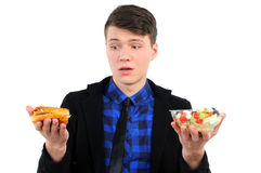 Fast food. Isolated young man with burgers and salad Royalty Free Stock Images