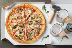 Fast food italiano A pizza quente deliciosa em uma caixa com presunto, cogumelos e vidro da cerveja cortou e serviu na tabela mar foto de stock