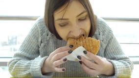 Fast food Jovem mulher com um apetite que come um hamburguer imagens de stock royalty free