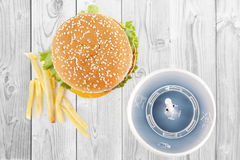 Fast food. Junk food burger fries soda sweet drink white table Stock Images