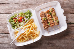 Fast food: kebabs, fries and fresh salad in the tray. horizontal Stock Images