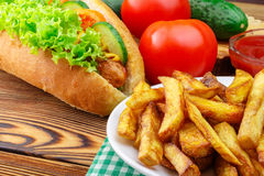 Fast food meal, hot dog, french fries, ketchup, tomato and cucumber on wooden background. Stock Photography