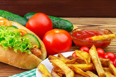 Fast food meal, hot dog, french fries, ketchup, tomato and cucumber on wooden background. Stock Image